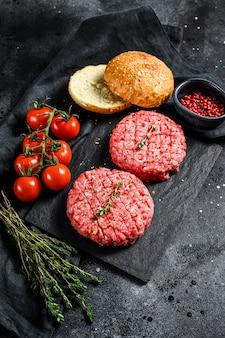 Ингредиенты для приготовления гамбургеров. фарш из говядины, булочки, помидоры, зелень и специи. вид сверху