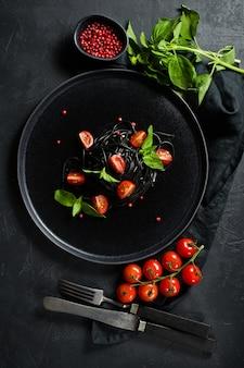 バランスの取れた健康食品、バジルとチェリートマトの黒スパゲッティ、ベジタリアンパスタ。