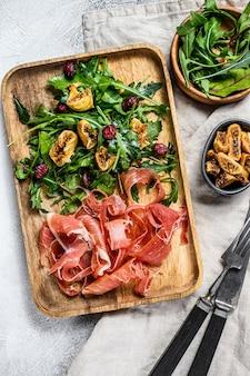 Салат с пармой, ветчиной прошутто, рукколой и инжиром. итальянские закуски. серый фон, вид сверху.