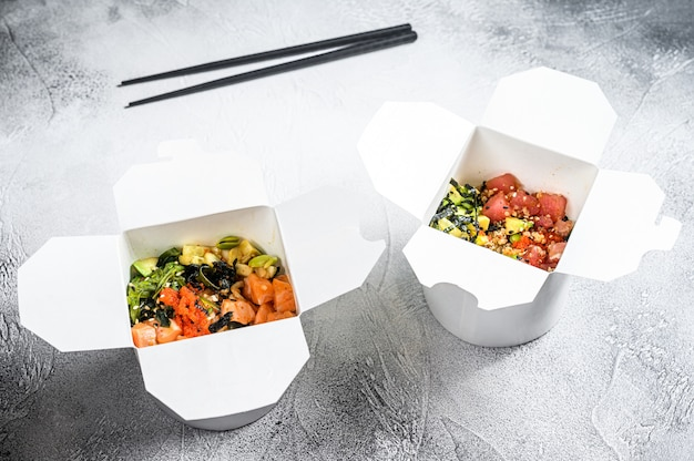 Шар будды в бумажной коробке с овощами, семгами и тунцом. уличная еда, чтобы пойти, забрать.
