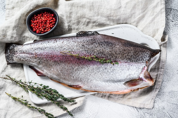 Сырая рыба радужная форель с солью и тимьяном. серый фон