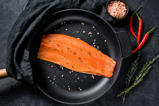 Сырое филе лосося с солью и перцем чили на сковороде. органическая рыба.
