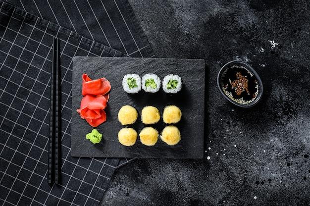 Различные виды суши подаются на черном камне. черный фон. вид сверху