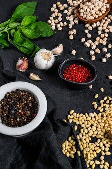 フムス成分、ニンニク、ひよこ豆、松の実、バジル、コショウ。黒の背景。上面図