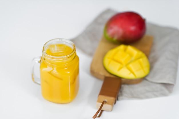 熟したマンゴーと木製のまな板にマンゴージュースのガラス。