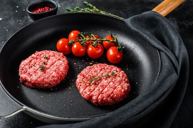 Сырой фарш из говяжьего мяса, котлеты в сковороде. ,