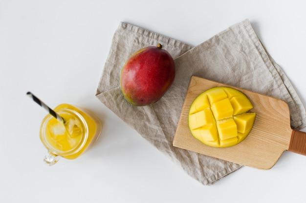 木製のまな板に熟したマンゴー、ハーフマンゴー、マンゴージュースのグラス。