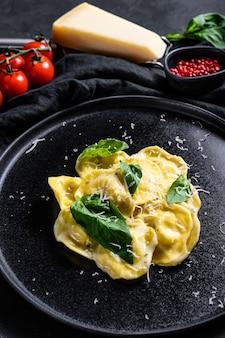 パルメザンチーズとバジルのラビオリのプレート。黒の背景。上面図