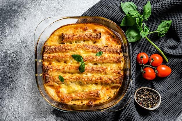 Каннеллони фаршированные соусом бешамель. макароны запеченные с мясом говядины, сливочным соусом, сыром. серый фон вид сверху