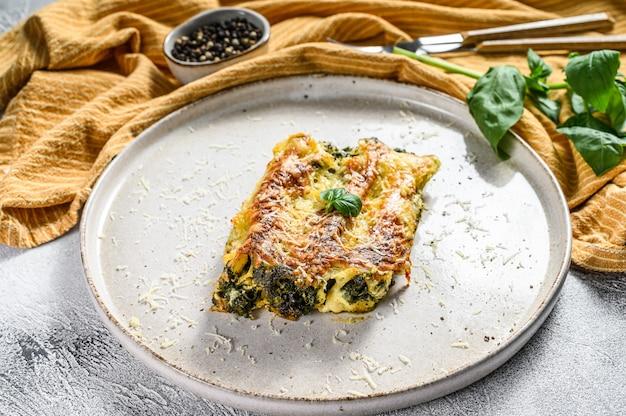 Запеченная фаршированная вегетарианская паста каннеллони с брокколи, шпинатом, базиликом и сыром. серый фон вид сверху.