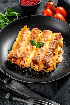 Итальянская домашняя паста каннеллони с говядиной и томатным соусом. черный фон. вид сверху