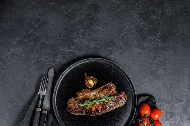 黒の背景に牛ストリップロースステーキ。テキストのためのスペース。マーブルビーフ。