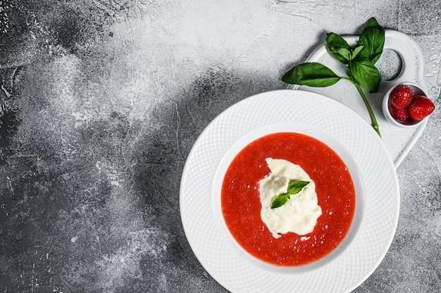 Десерт из клубничного пюре и сыра моцарелла. серый фон пространство для текста