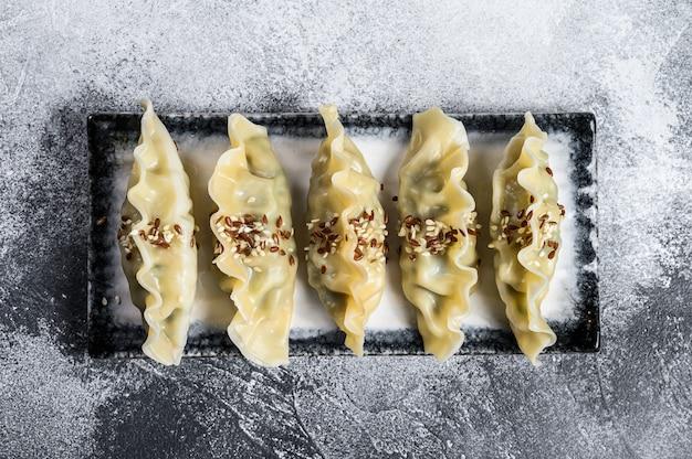 セラミックプレートに韓国餃子を蒸します。灰色の背景。上面図