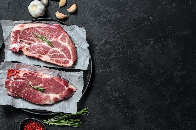 生のポークステーキ。羊皮紙に大理石の肉。黒の背景。上面図。テキストのためのスペース
