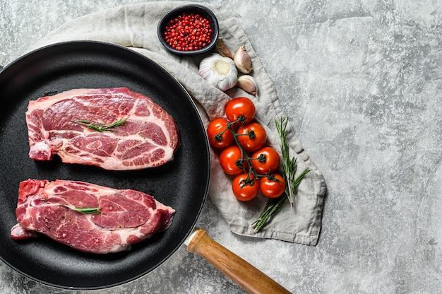 フライパンで新鮮なポークステーキ。霜降りの農場の肉。灰色の背景。上面図。テキストのためのスペース