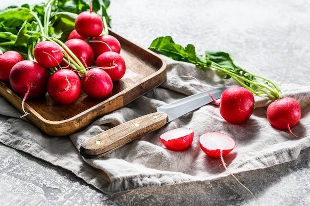 Свежие красные редиски в деревянной миске. ферма органических овощей. серый фон вид сверху