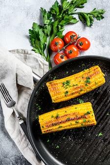 フライパンで有機焼きトウモロコシ。有機農場野菜。灰色の背景。上面図