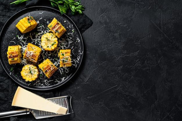 パセリとパルメザンチーズをまぶしたトウモロコシのグリル焼き。黒の背景。上面図。テキストのためのスペース