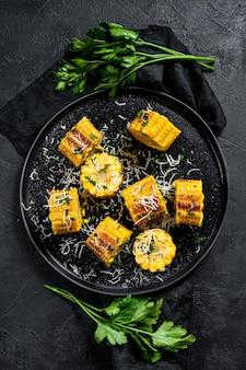 パルメザンチーズとパセリを焼いたスイートコーン。有機農場野菜。黒の背景。上面図