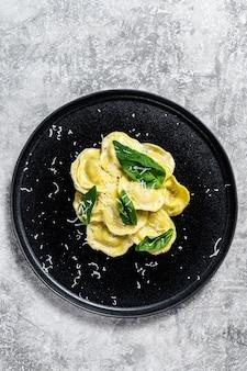 チーズとバジルのイタリアンラビオリパスタ。灰色の背景。上面図