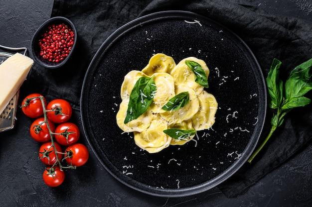 チーズとほうれん草の伝統的なイタリアのラビオリ。黒の背景。上面図