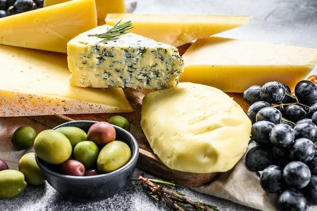 ナッツオリーブとブドウのチーズのさまざまな部分。おいしいスナックの盛り合わせ。灰色の背景。上面図