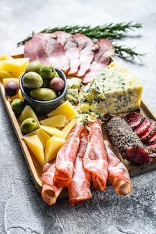 イタリアの前菜または前菜は、チーズと肉のスナックの混合デリカテッセンを設定します。灰色の背景。上面図