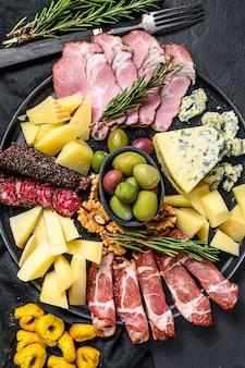 Антипасто с ветчиной, прошутто, салями, голубым сыром, моцареллой и оливками. черный фон. вид сверху
