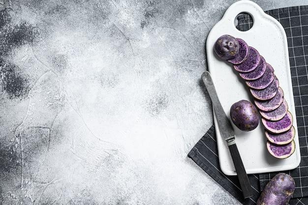 白いまな板に生のスライスした紫ジャガイモ。灰色の背景。上面図。テキストのためのスペース