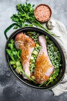 七面鳥のシチュー。パセリ、エンドウ豆、セロリ、ジャガイモのバチのレシピ。灰色の背景。上面図