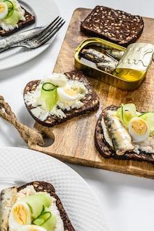 Вкусные закуски-тапас, всмятку и консервированные бутерброды с сардинами. салат со шпинатом и вялеными помидорами. белый фон. вид сверху