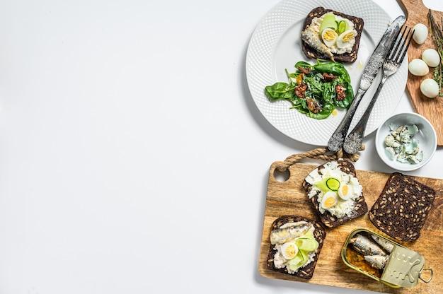 Бутерброды с сардинами, яйцом, огурцом и сливочным сыром, гарнир к салату со шпинатом и вялеными томатами. белый фон. вид сверху. копировать пространство