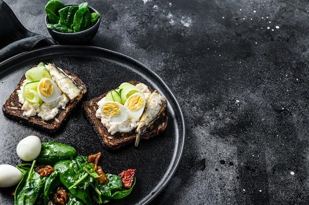 Бутерброды с сардинами, яйцом, огурцом и сливочным сыром, гарнир к салату со шпинатом и вялеными томатами. черный фон. вид сверху. копировать пространство