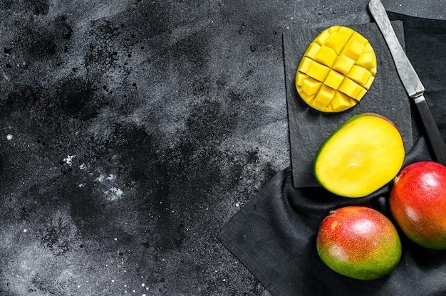 Спелый плод манго, нарезанный кубиками. черный фон. вид сверху. копировать пространство