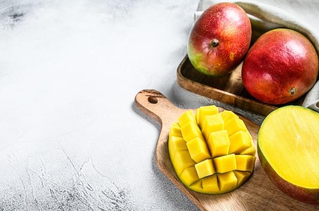 Спелые нарезанные фрукты манго на разделочную доску. серый фон вид сверху. копировать пространство