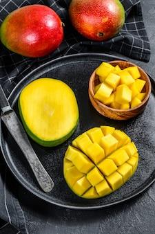 Спелое манго. нарезать кубиками тропические фрукты. черный фон. вид сверху