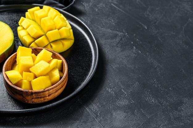 Спелое манго. нарезать кубиками тропические фрукты. черный фон. вид сверху. копировать пространство