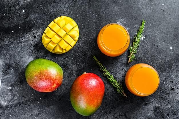 Свежевыжатый сок манго в стакане. черный фон. вид сверху