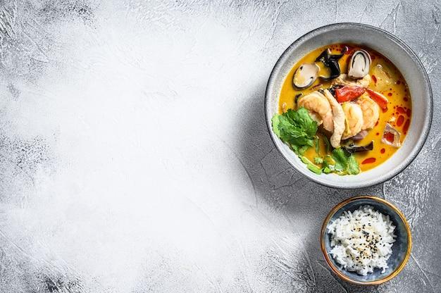 エビとココナッツミルクのトムヤムスープ。灰色の背景。上面図。コピースペース