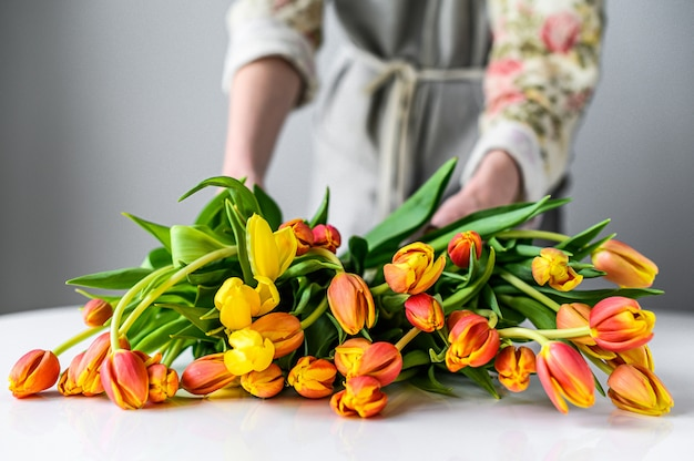 Флорист на работе. женщина делает букет из весенних тюльпанов цветов. белый фон