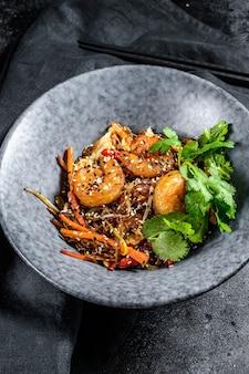 海老と野菜を炒めたライスヌードル。アジアの中華鍋。黒の背景。上面図