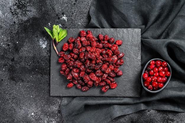 赤い乾燥クランベリーと新鮮なミントの葉。オーガニックベリー。黒の背景。上面図。