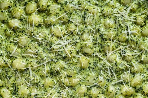 ニョッキとバジルのほうれん草ソース。イタリアンポテトペースト。灰色の背景。上面図。