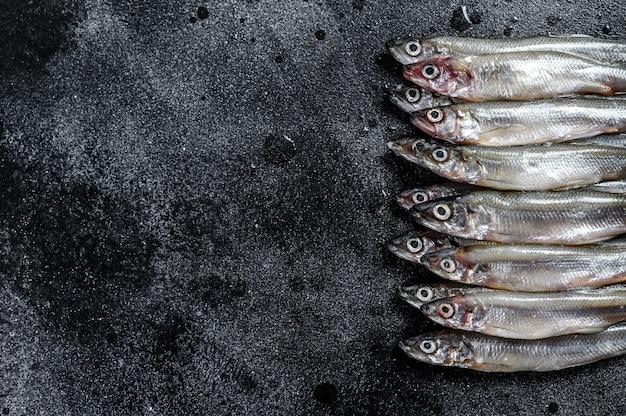 新鮮な生の海の小さな魚のワカサギ。黒の背景。上面図。コピースペース