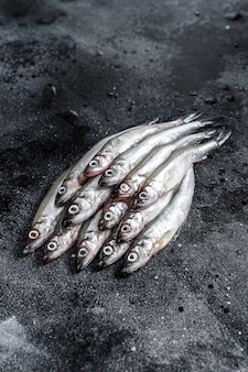 新鮮な生の海の小さな魚のワカサギ。黒の背景。上面図