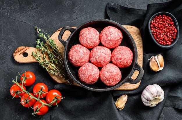 Рецепт приготовления фрикадельок из говяжьего фарша на сковороде. черный фон. вид сверху