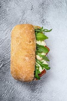 Бутерброд со свежим сыром камамбер, грушевым мармеладом, рикоттой и рукколой. серая поверхность. вид сверху