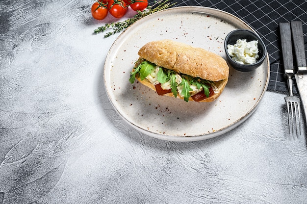 Бутерброд со свежим сыром камамбер, грушевым мармеладом, рикоттой и рукколой. серая поверхность. вид сверху. пространство для текста