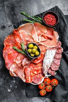 Ассорти из испанского холодного мяса. чоризо, фут, поясница, хамон иберико, оливки. черная поверхность. вид сверху.